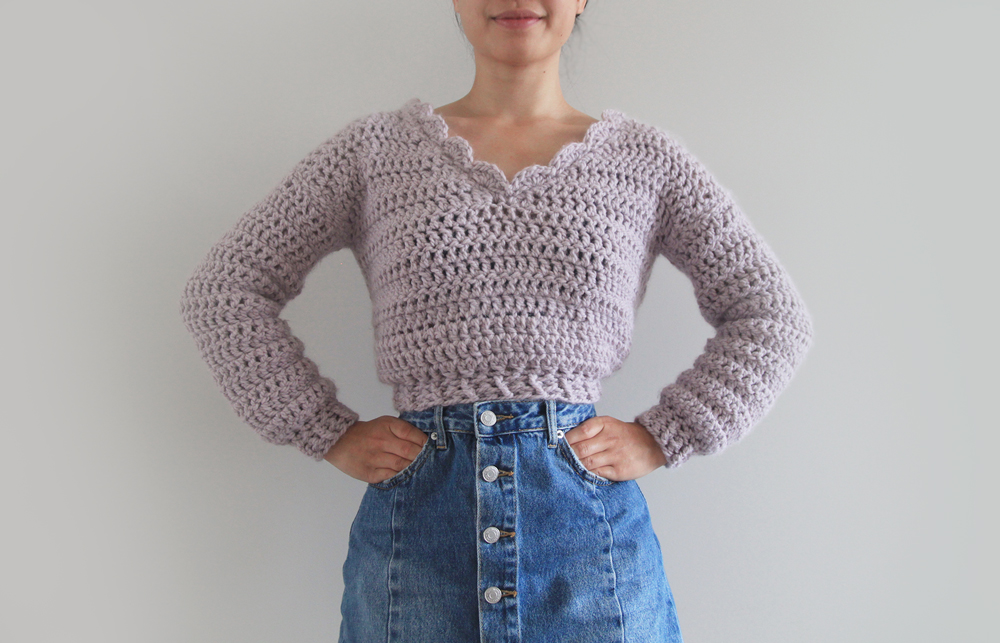 model wearing chunky crop pullover with scallop neckline and blue denim skirt