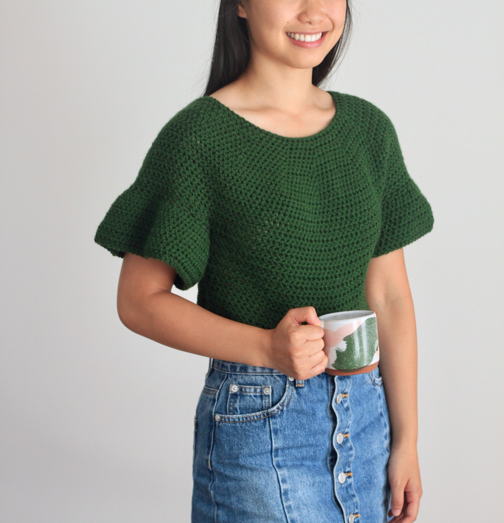 model wearing hunter green crochet top with ruffle sleeves and holding a mug