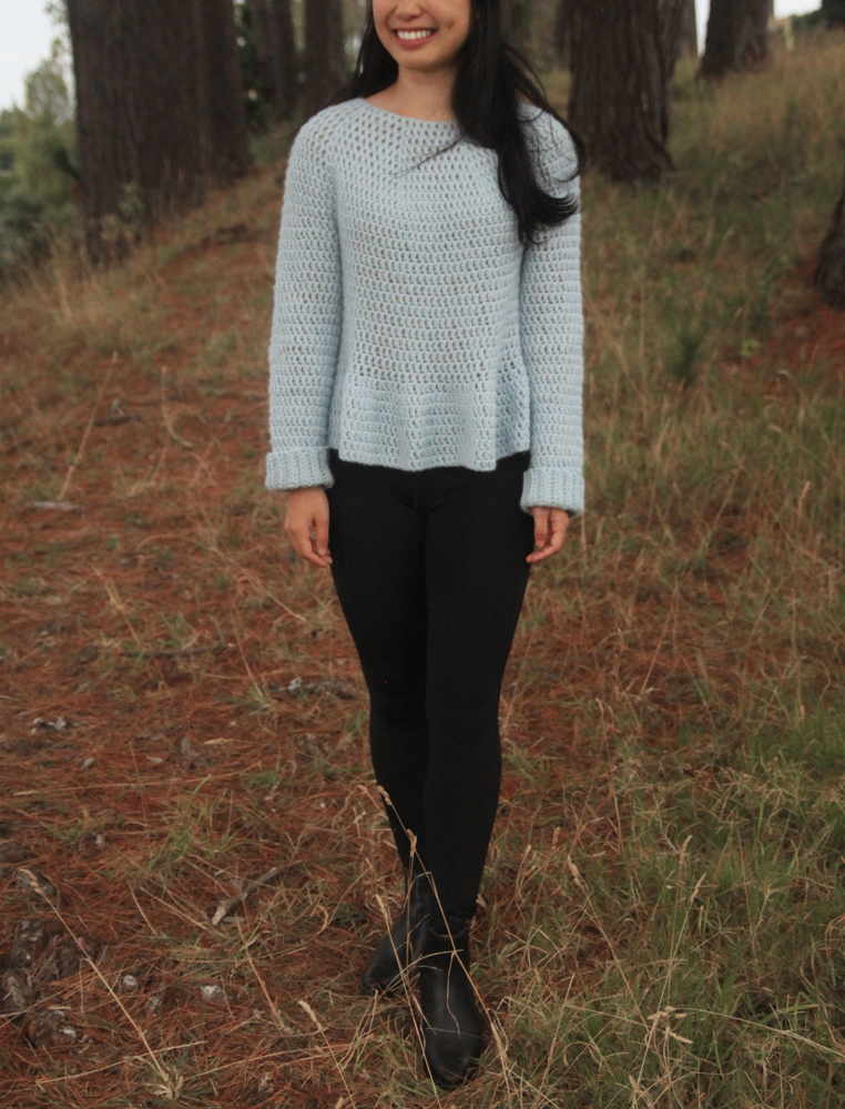woman light blue peplum crochet sweater with black leggings and ankle boots