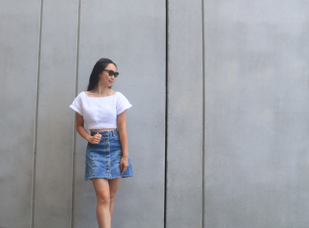 model wearing summer outfit with simple crochet crop top denim skirt and sunglasses