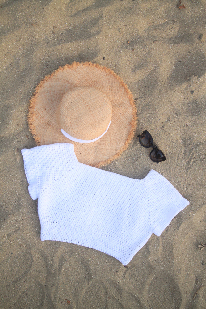 flat lay of white crochet crop top with sun hat and sunglasses on beach sand