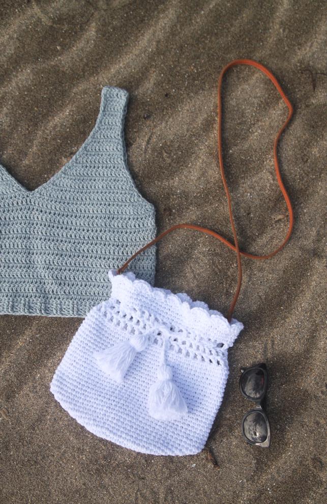 white cotton crochet bucket bag laying on sand