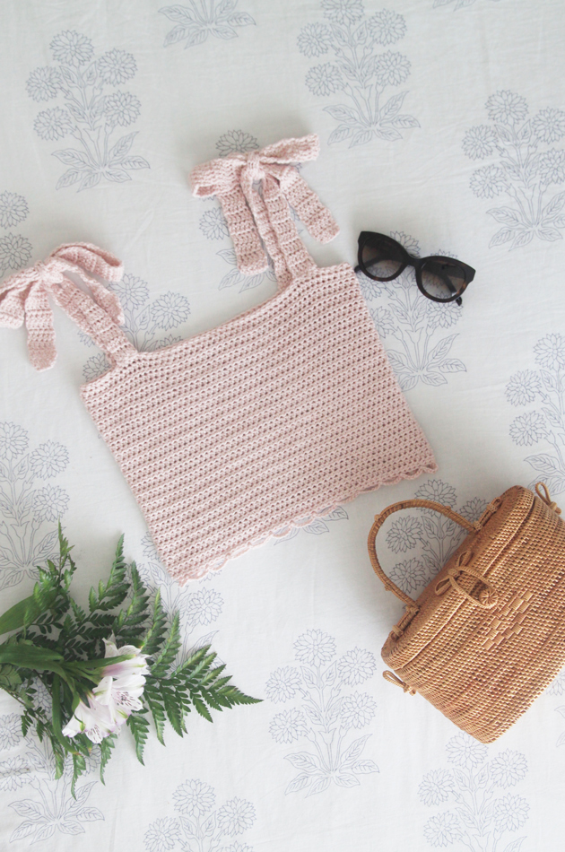 flat lay of pink crochet crop top, rattan bag, flowers and sunglasses