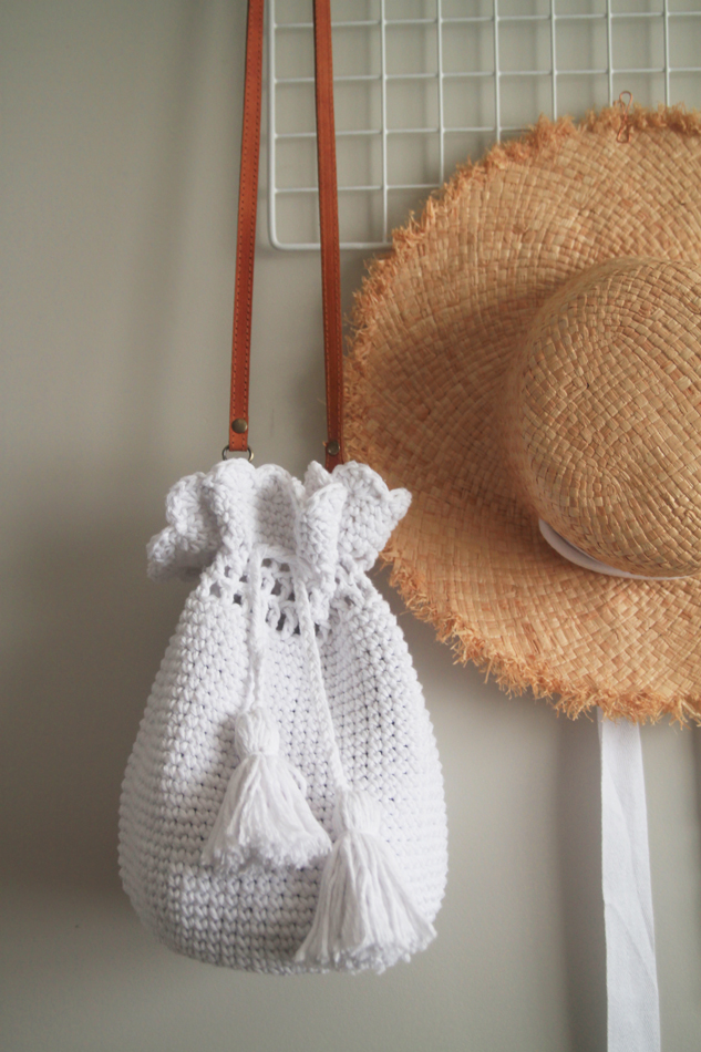 crochet bucket bag hanging in front of straw hat