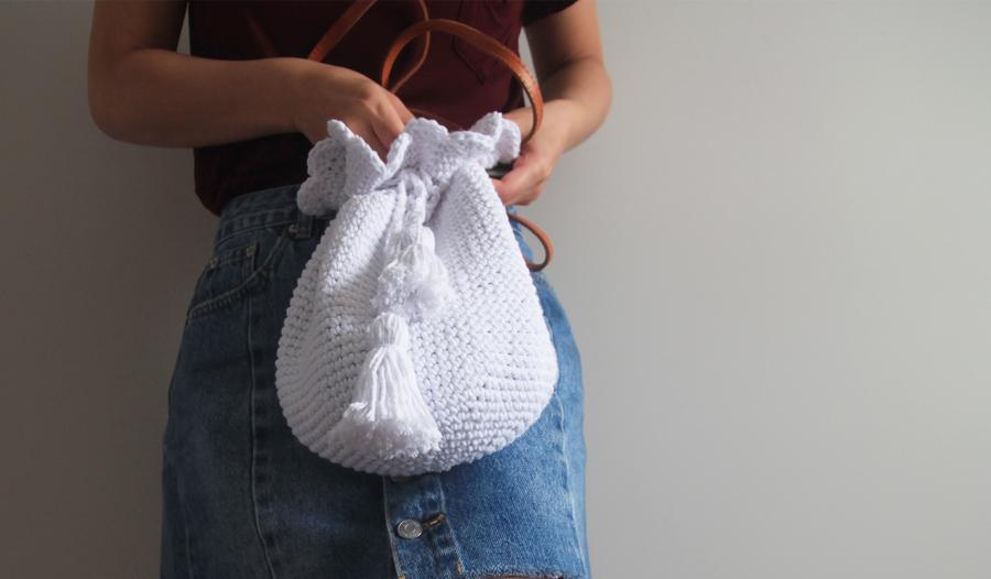 woman opening crochet bucket bag