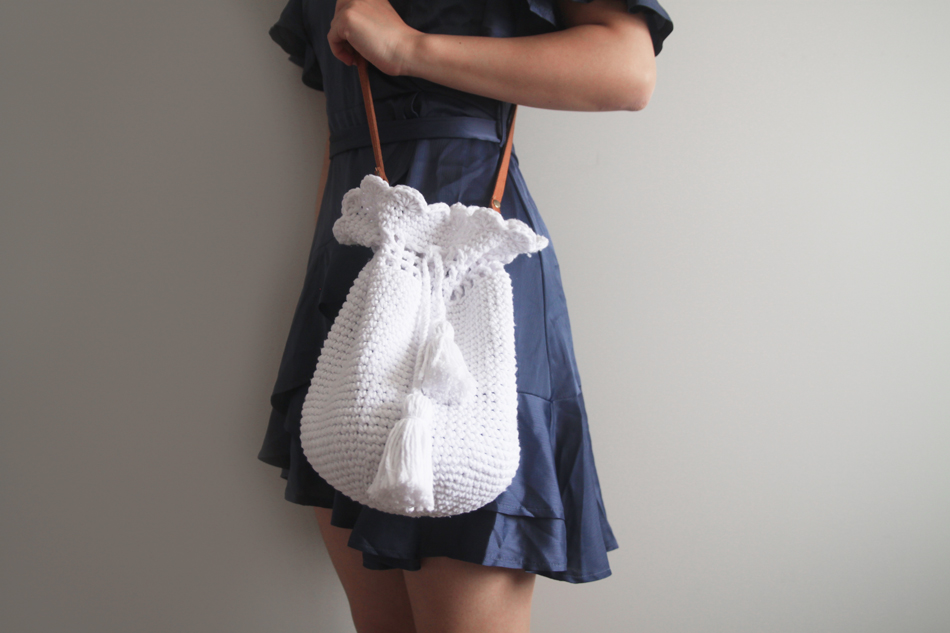 woman holding crochet bucket bag with scallop stitch and chunky tassels