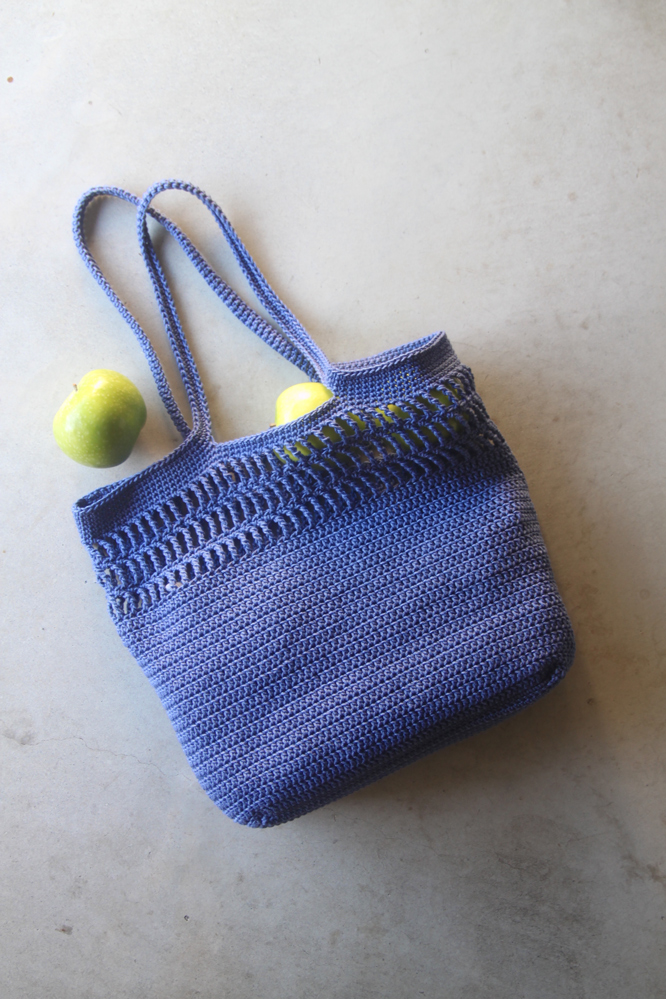 blue cotton crochet tote bag with green apples rolling out