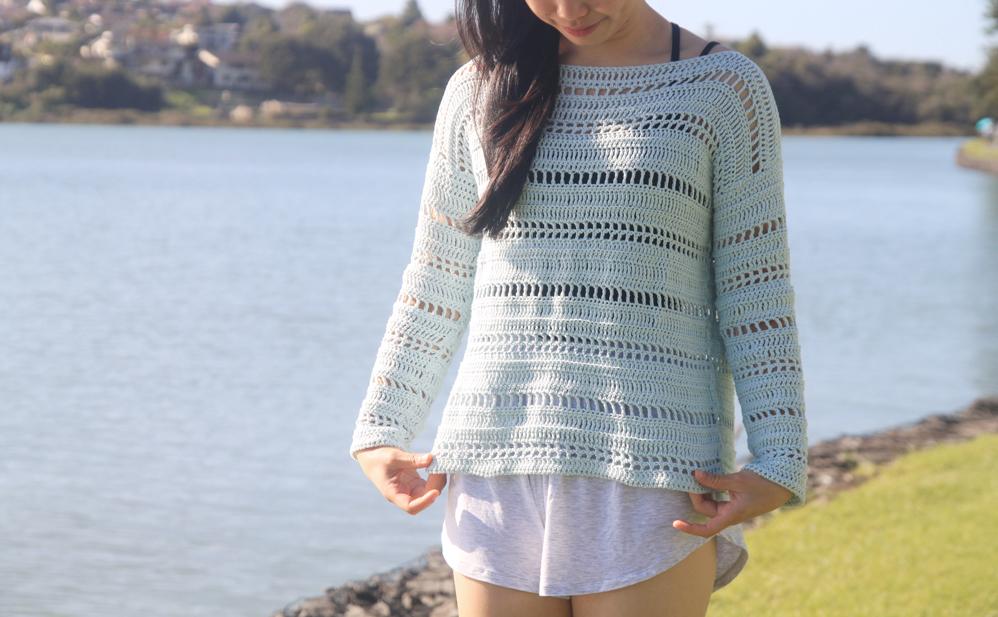 woman holding hem of crochet mesh sweater
