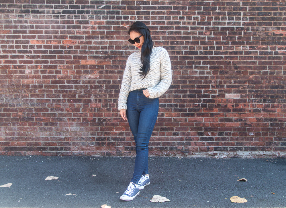 woman wearing super bulky crochet sweater with jeans and converse sneakers