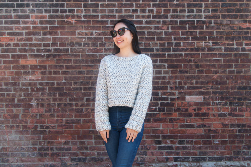 woman wearing chunky crochet jumper with sunglasses and blue denim jeans