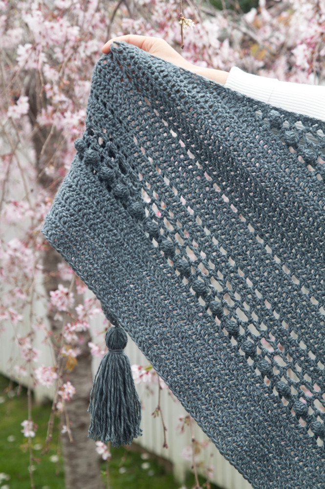 close up of grey crochet wrap with tassels and bobbles with cherry blossom background