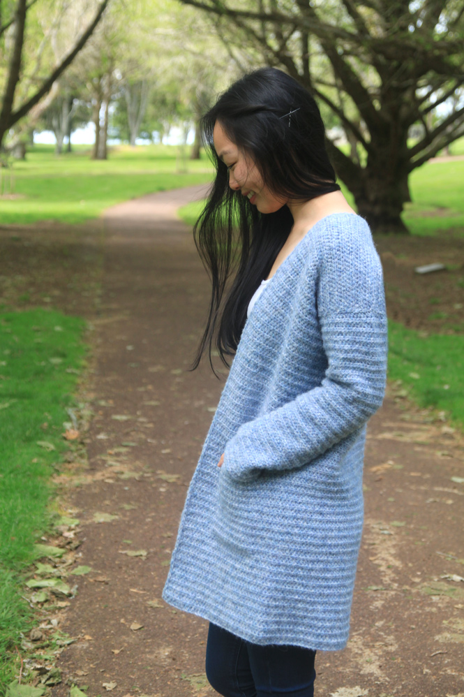 side view of blue crochet coat with pockets with video tutorial