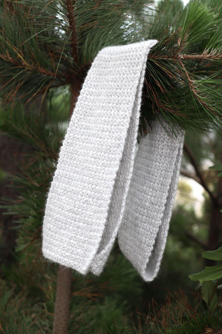 beginner crochet scarf pattern hanging on pine tree branch