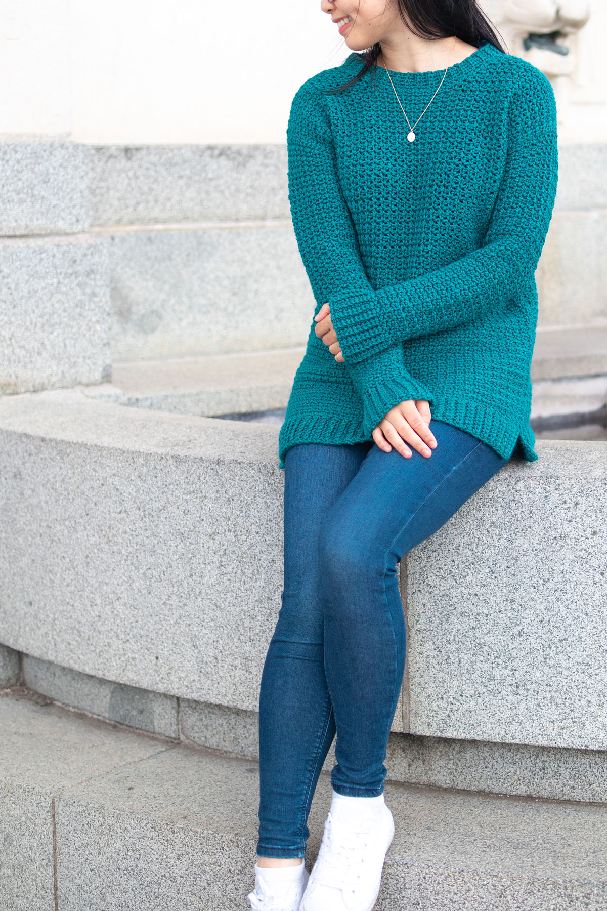 long crochet sweater green pullover blue jeans sitting on ledge