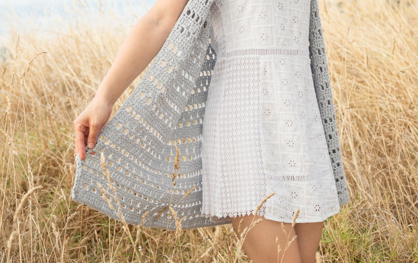 close up of easy crochet lace stitches in a grey cardigan pattern with a white dress