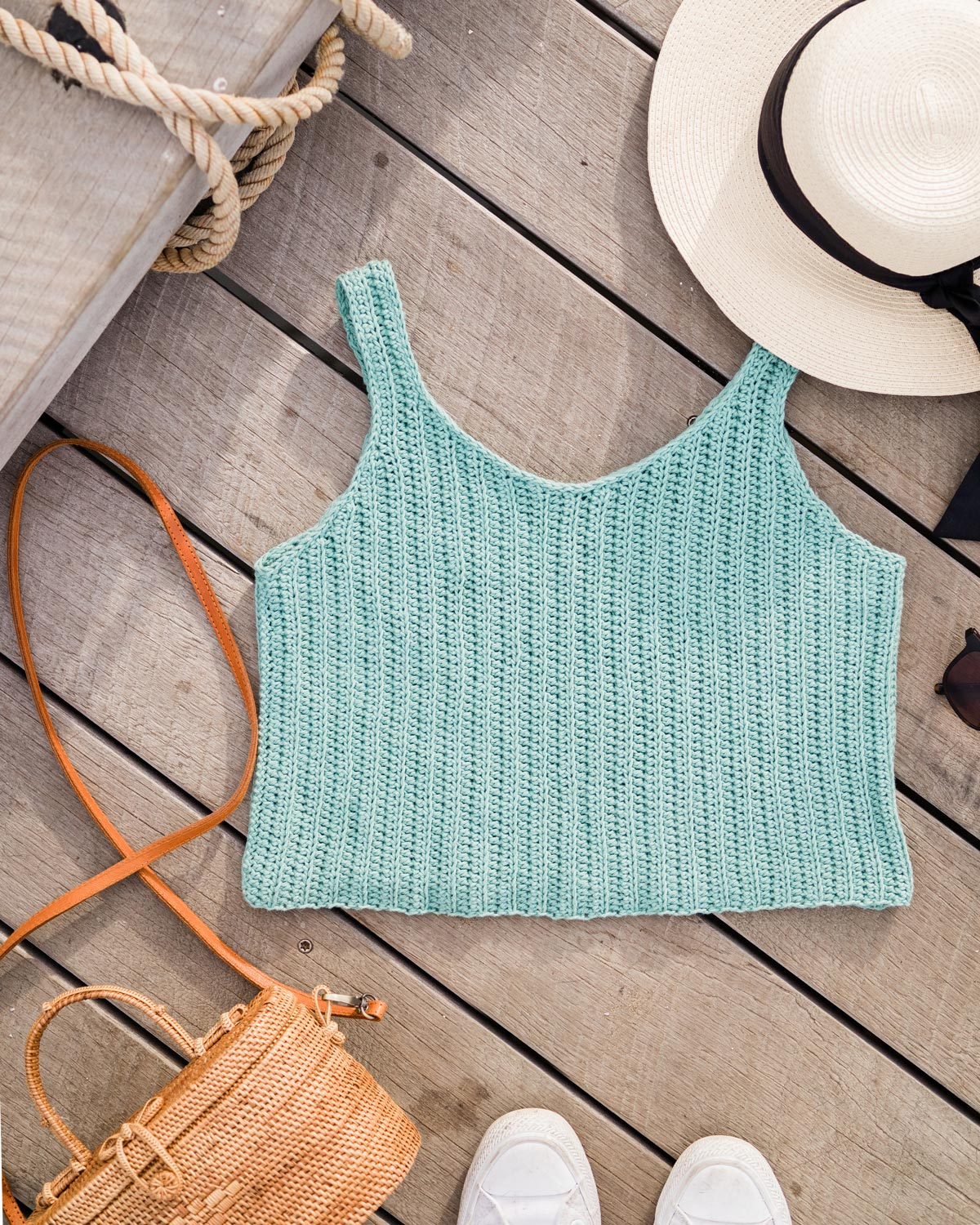 flat lay of sage green ribbed crochet singlet with straw hat and rattan bag