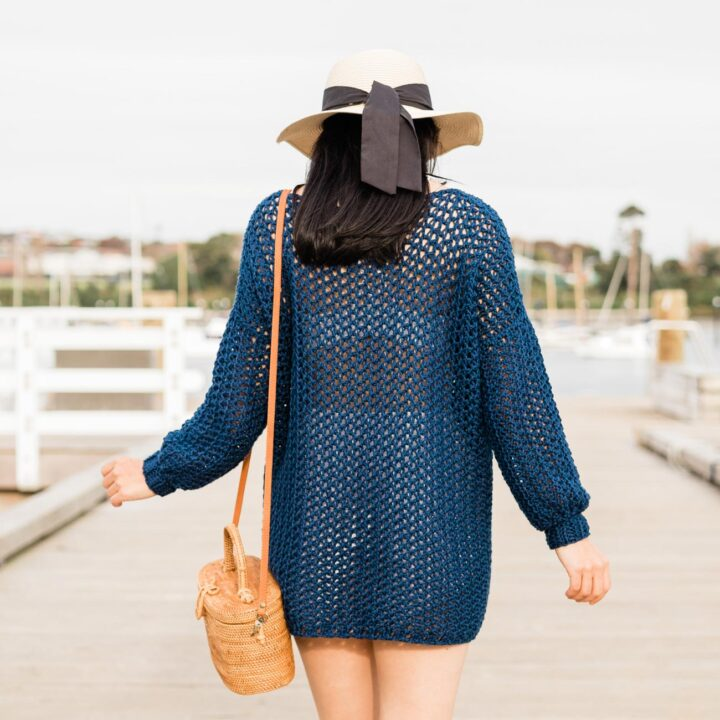 close up of beach cover up crochet sweater with straw hat and rattan bag