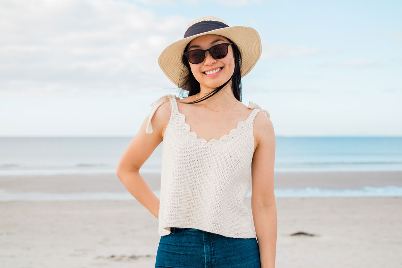 woman wearing cream crochet v-neck tie strap tank top with straw hat and blue jeans