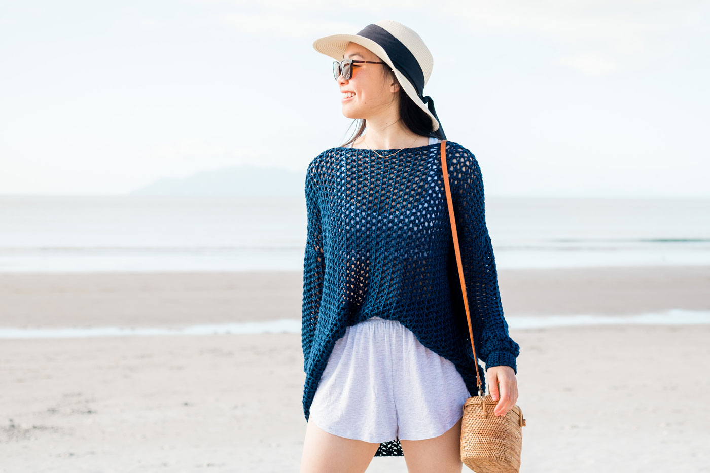 simple crochet cover up tucked into grey shorts with sun hat and rattan bag
