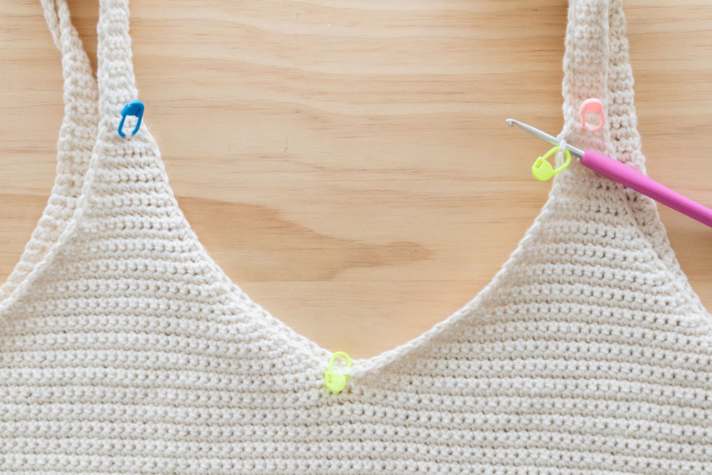 crochet hook inserted into stitch with stitch marker at the top of v neckline on tank top