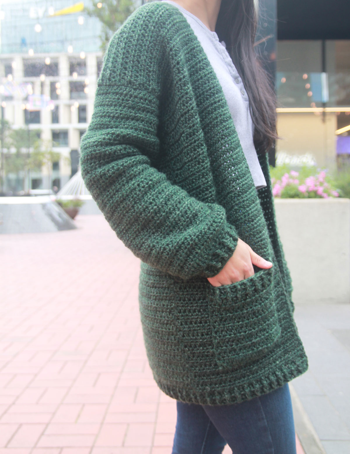 close up of crochet pocket on forest green oversized cardigan