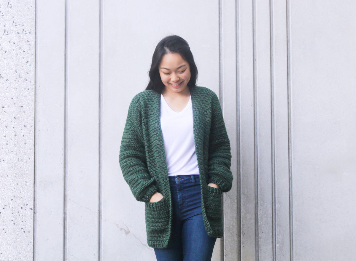 model with hands in pockets of slouchy crochet cardigan