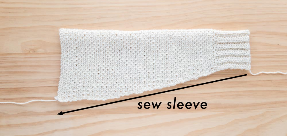 crochet sleeve folded in half to whip stitch long edge together