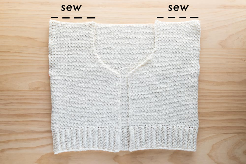 front panels of crochet cardigan folded on top of back panel to whip stitch shoulder seams together