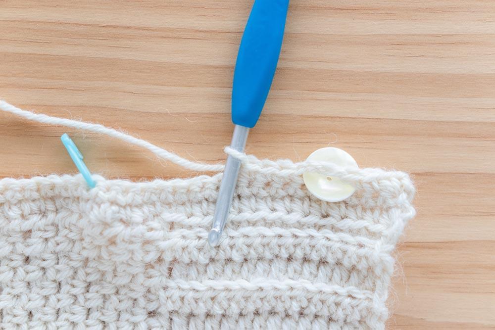 cream pearl button inserted into crochet button along cardigan neckline