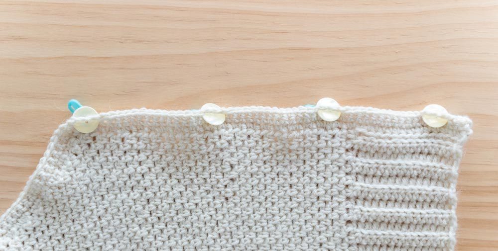 pearl buttons inserted into crochet button holes along cardigan edging