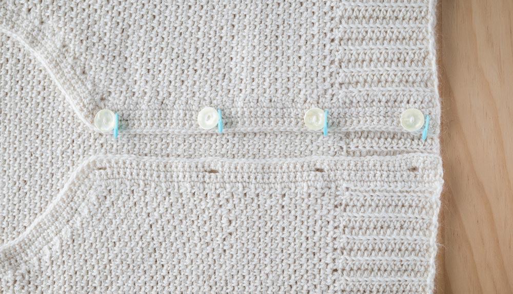 buttons sewn onto crochet cardigan neckline