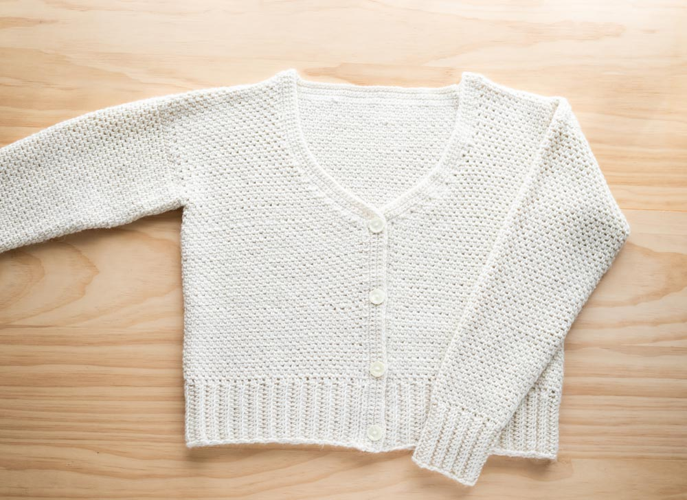 flat lay of v neck crochet cardigan with buttons and knit look ribbing