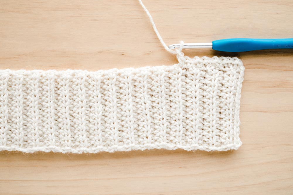 close up of moss stitch along back loop half double crochet band with crochet hook
