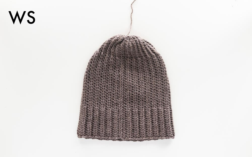 wrong side of basic crochet beanie with top opening sewn closed