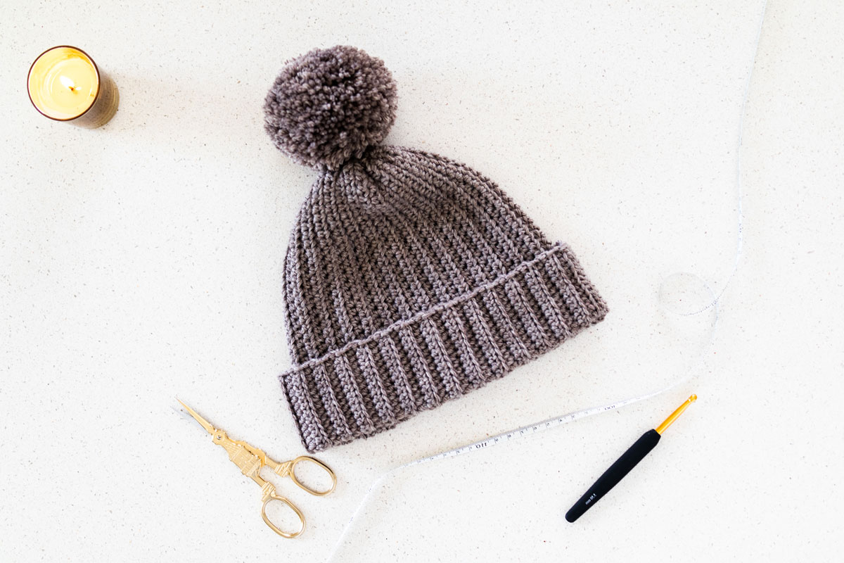 flat lay of ribbed crochet beanie with pom pom, embroidery scissors and gold crochet hook