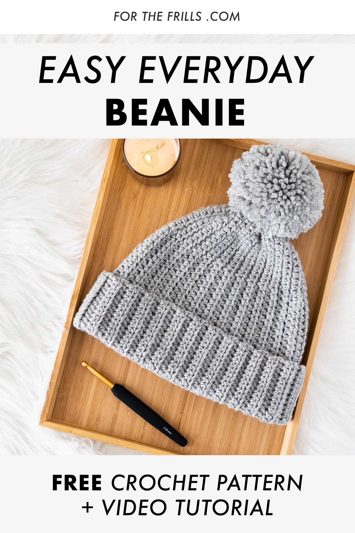 flat lay of simple tapered crochet beanie with pom pom and gold crochet hook