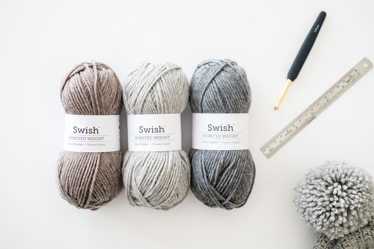 flatlay of wecrochet swish worsted merino yarn in the shades squirrel heather brown, dove heather light grey and marble heather gray
