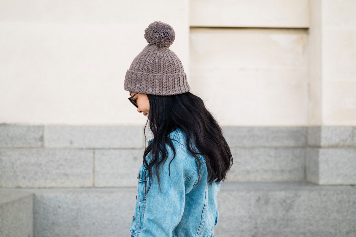 model wearing brown merino crochet pom pom beanie and denim jacket