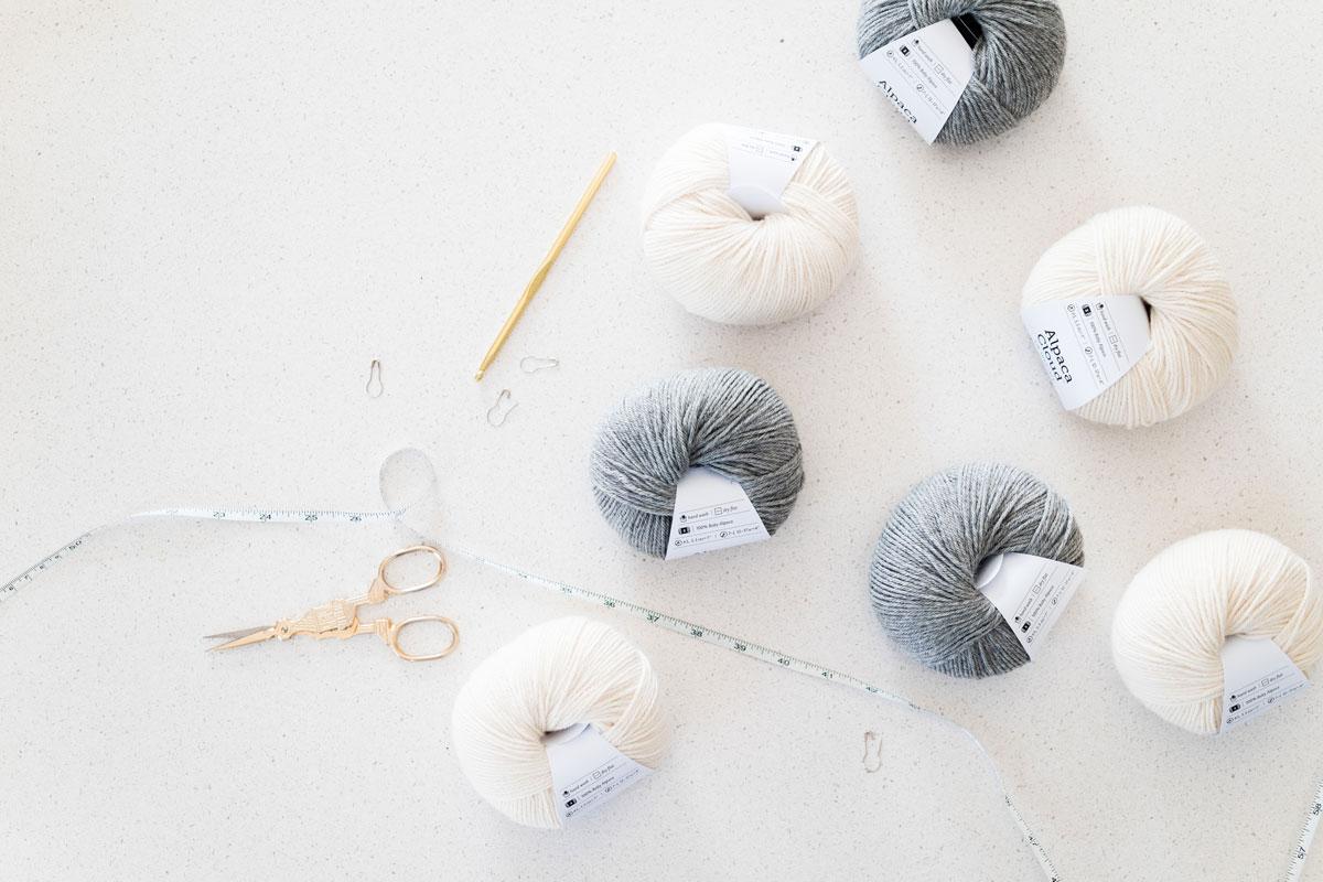 flat lay of knit picks we crochet alpaca cloud DK yarn in shades sophia cream and alfred medium grey