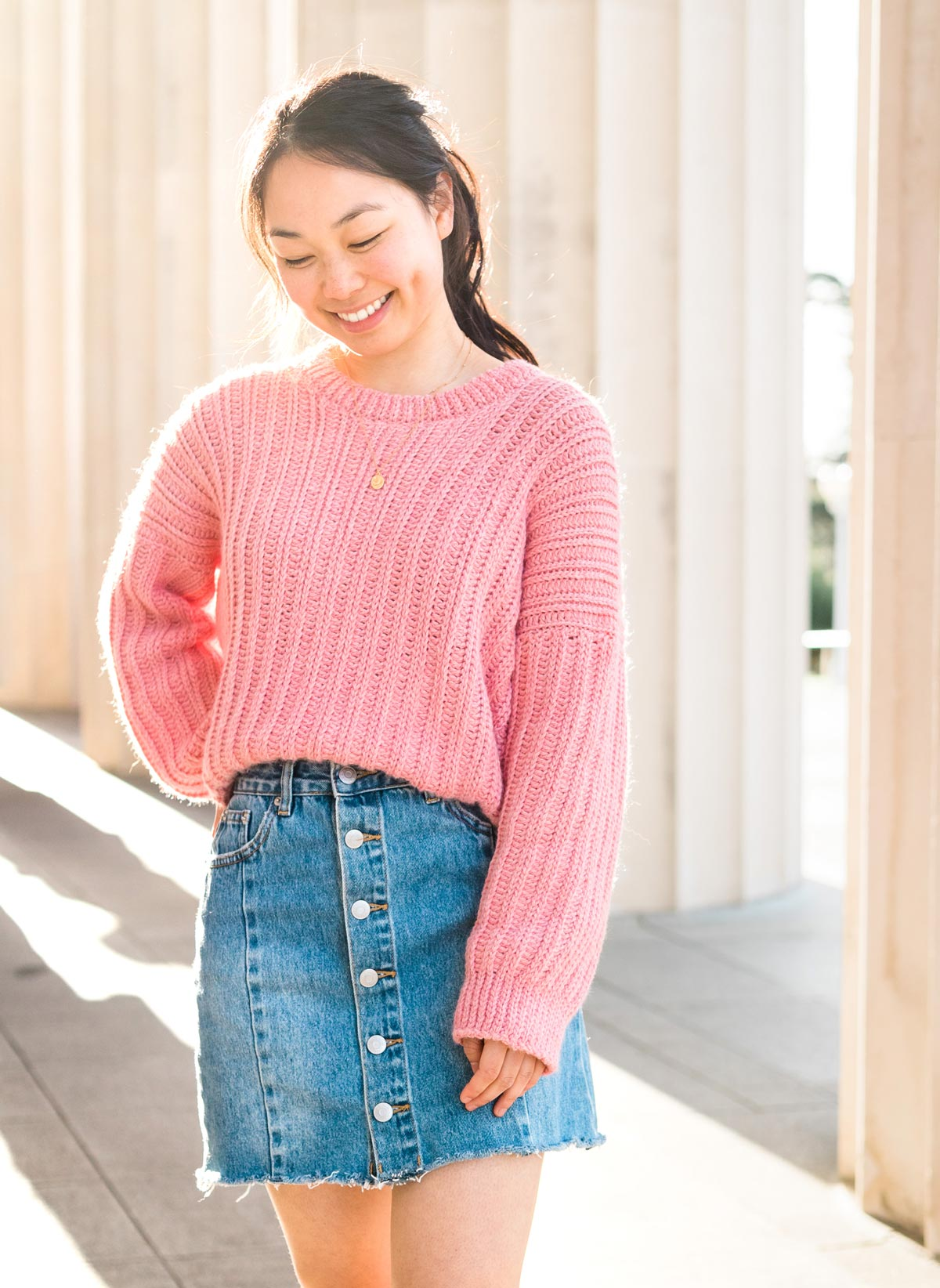 oversized crochet sweater with knit-like stitches with denim mini skirt and gold necklace