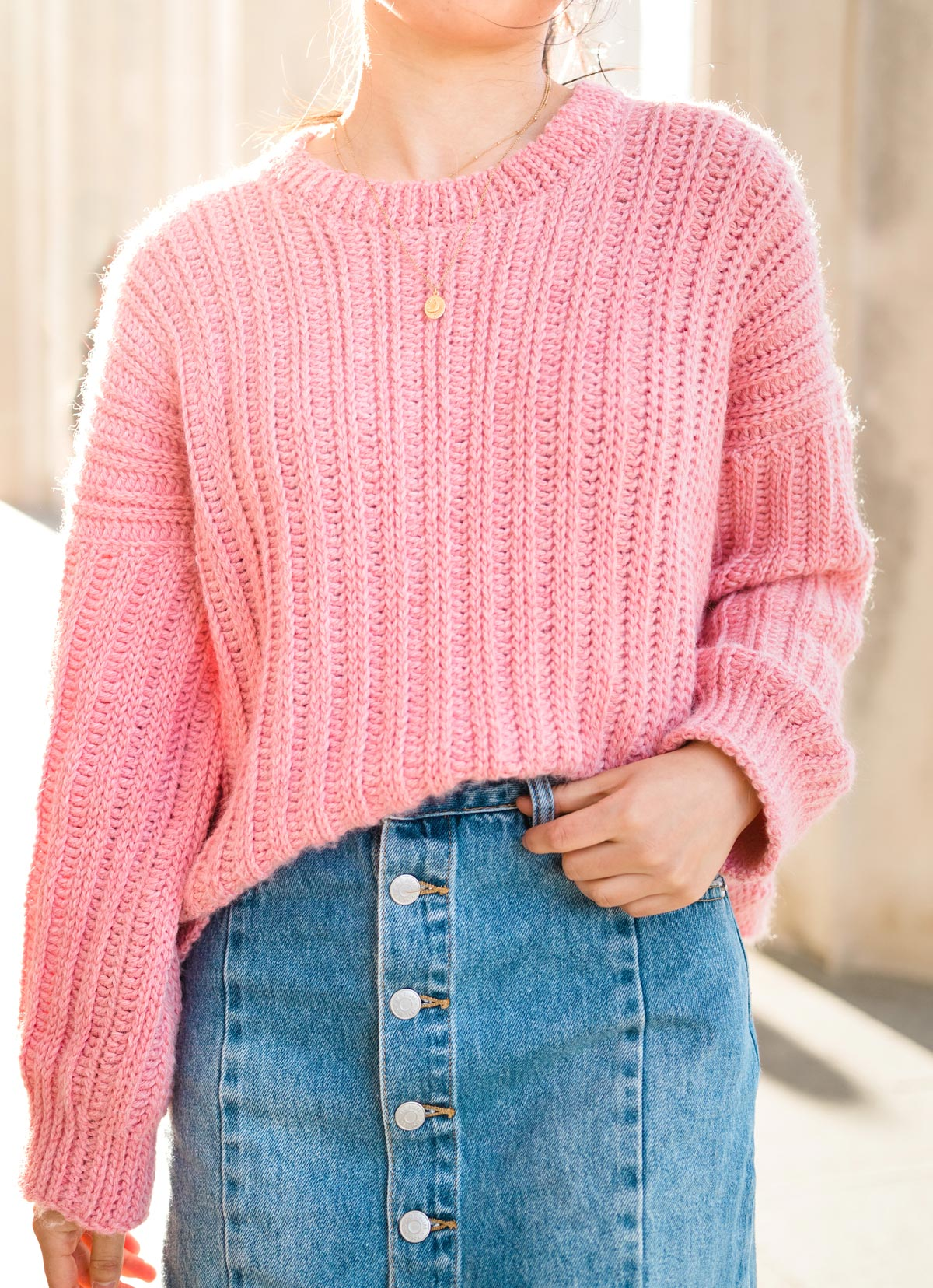 close up of ribbed oversized crochet sweater tucked into denim button down skirt