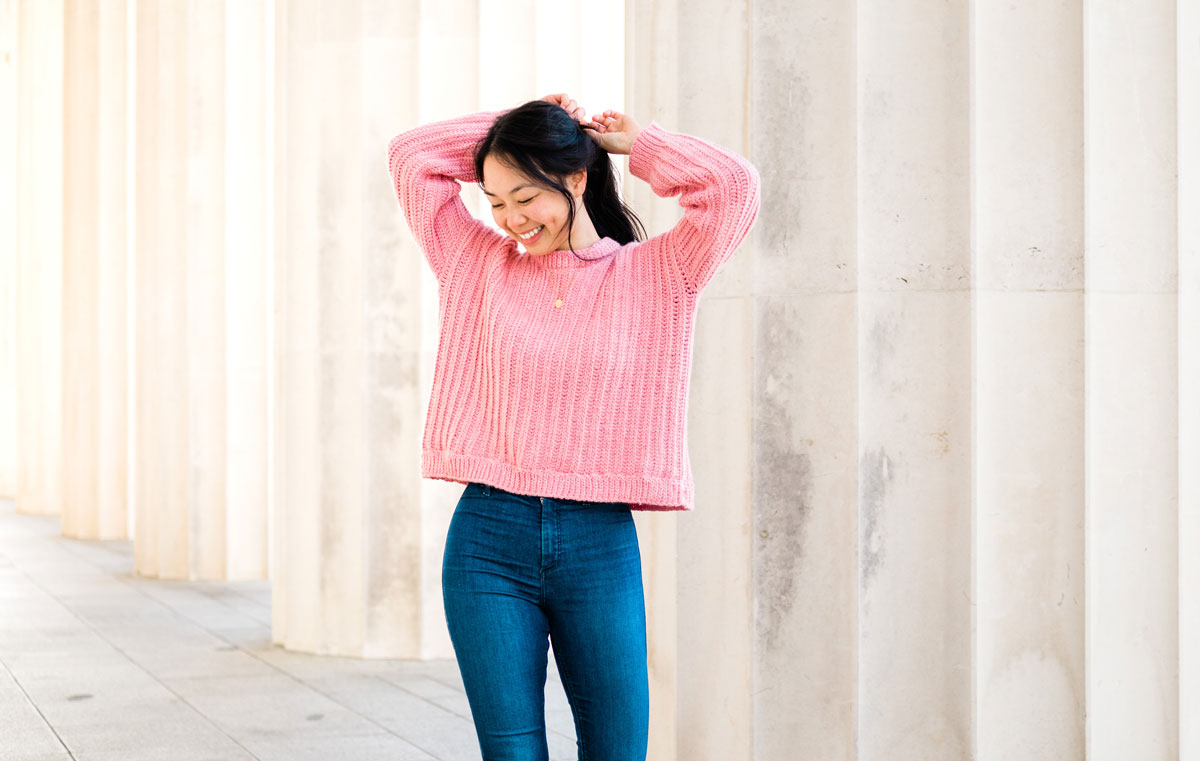 model wearing ribbed crochet sweater with blue jeans and arms behind head