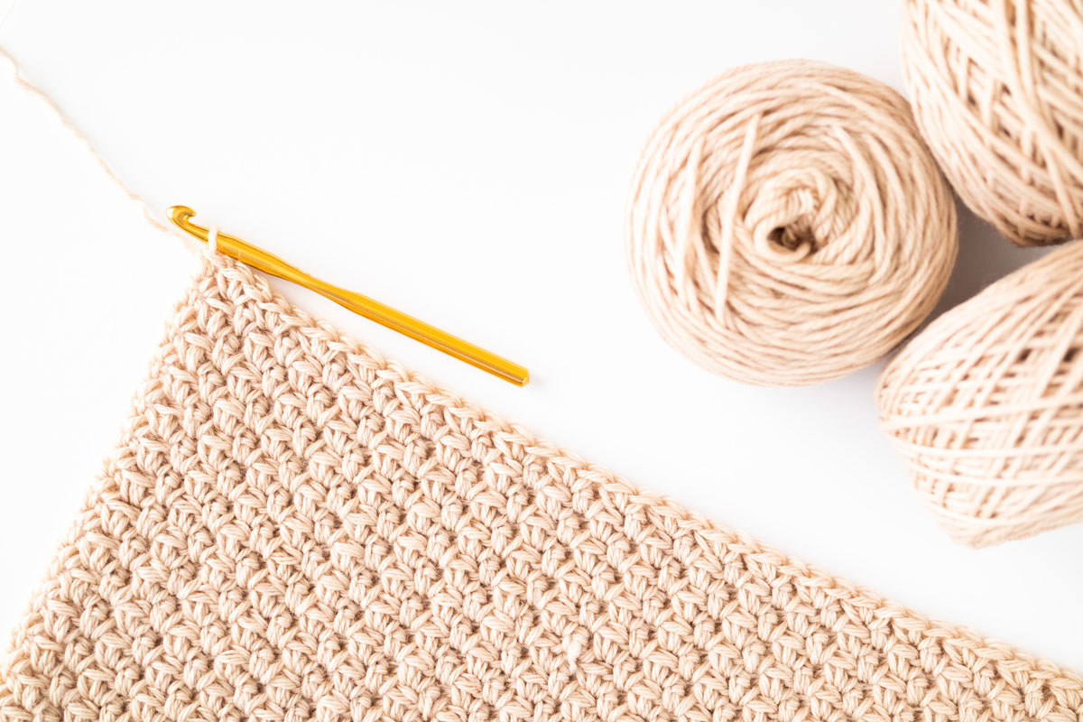 flat lay of chunky crochet cluster moss stitch with gold crochet hook and skeins of wool yarn