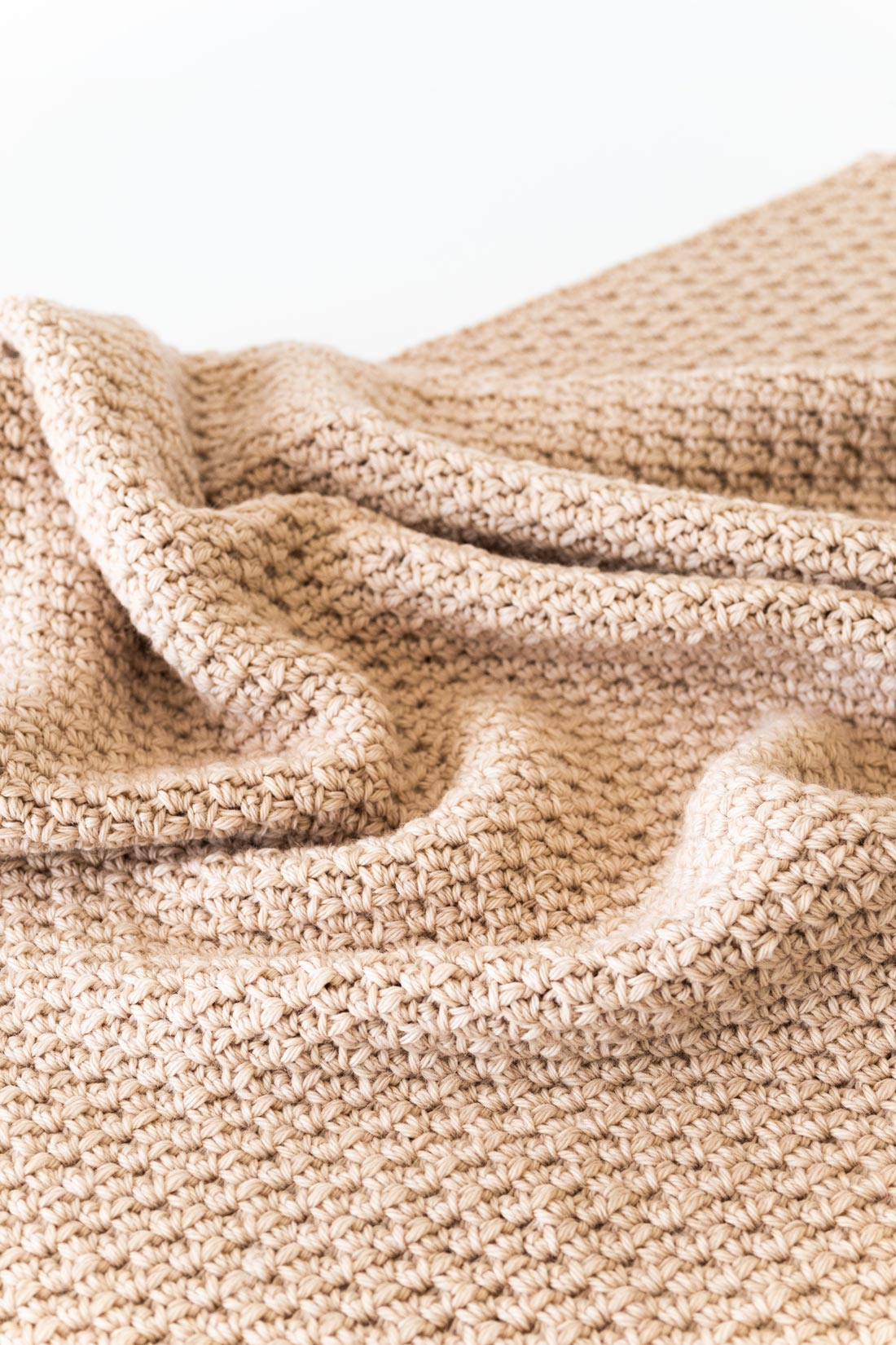 close up on textured chunky crochet throw made of cluster linen stitch