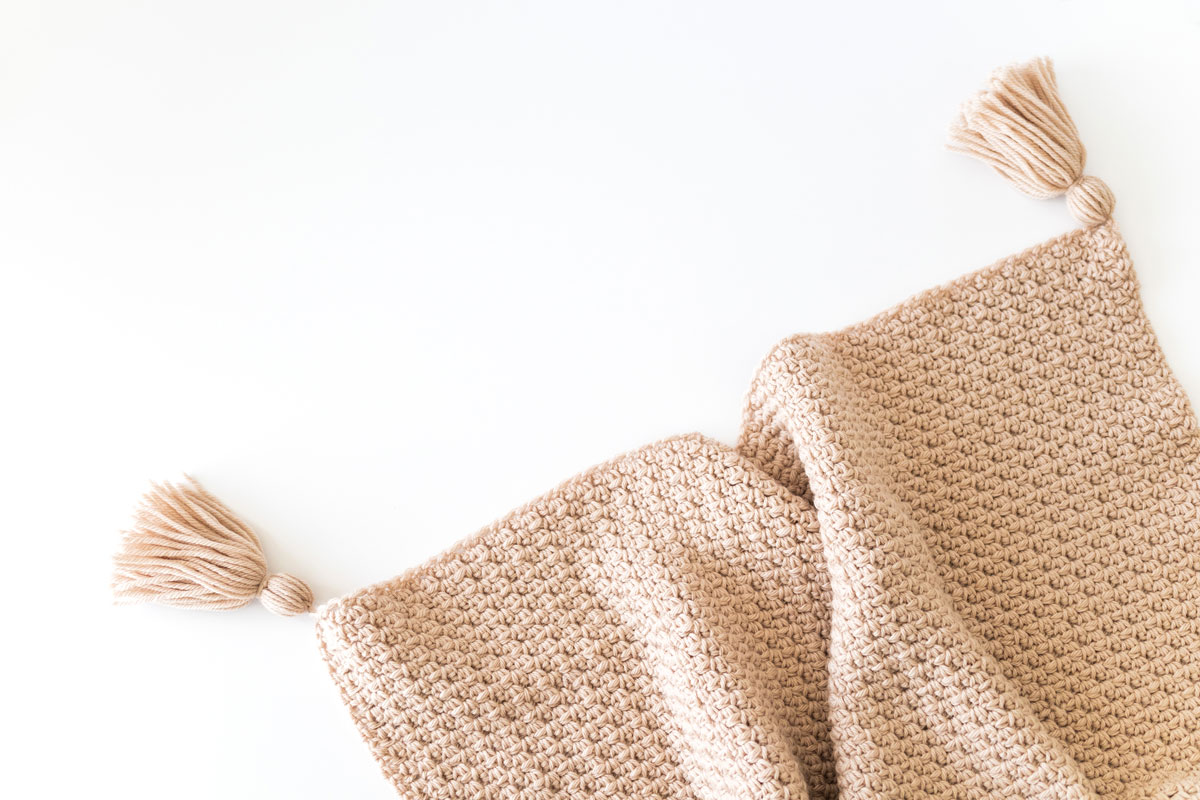 cosy crochet blanket with tassels and modern textured stitches