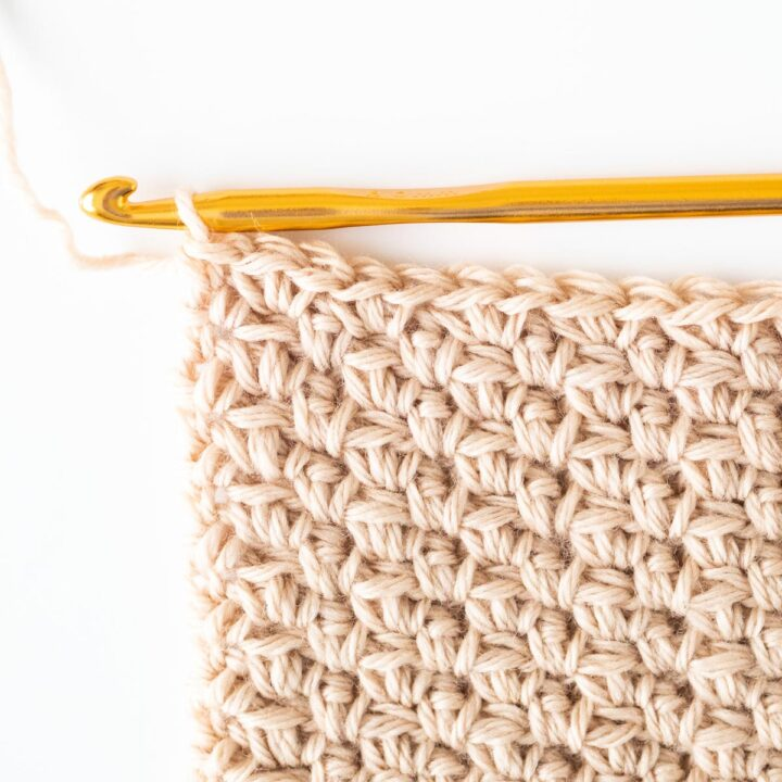 close up on cluster linen stitch with gold crochet hook
