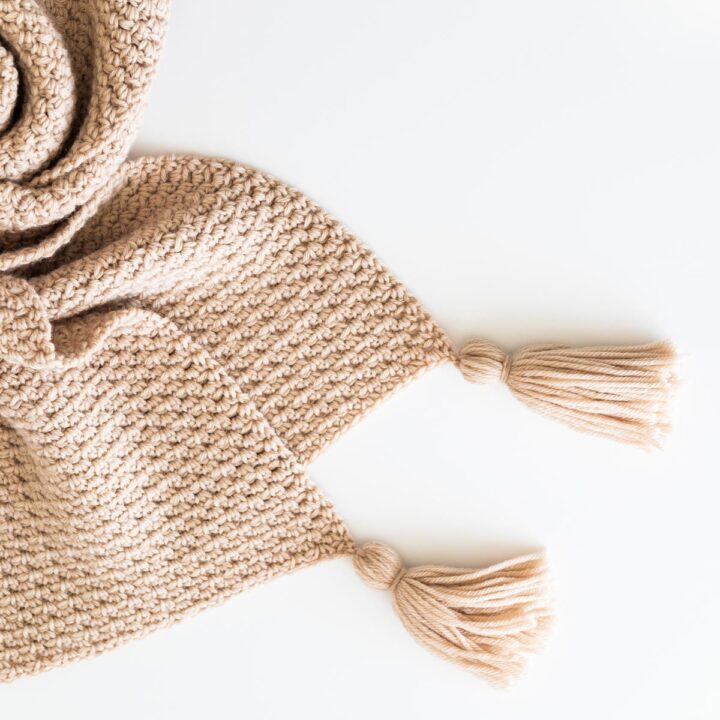 curled up textured crochet blanket with chunky tassels in cluster moss stitch