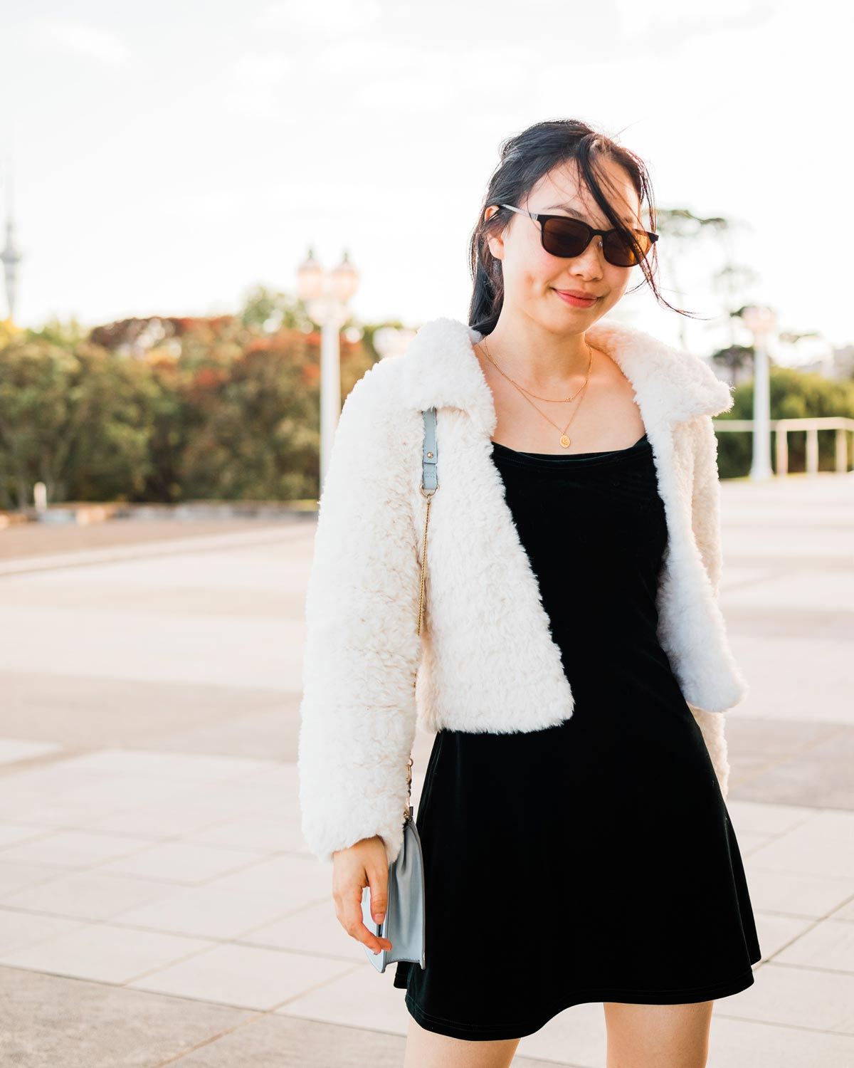white faux fur crochet coat with collar and blue handbag