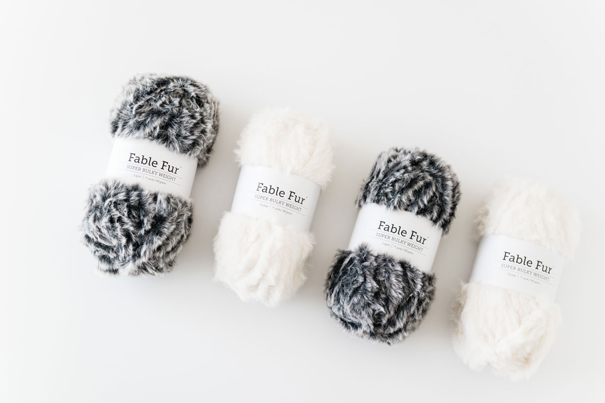 flat lay of we crochet super bulky cream faux fur yarn and black faux fur yarn with white highlights