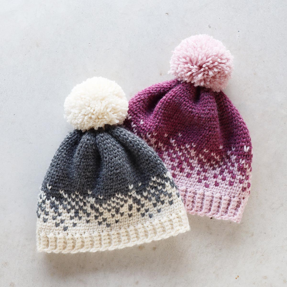 flat lay of fair isle crochet beanies with ribbed brim and pom poms in grey and white and light pink and magenta